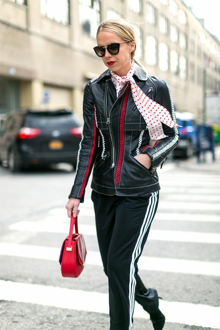 Pantalone nero sportivo in combinazione alla giacca di pelle, borsetta di colore rosso