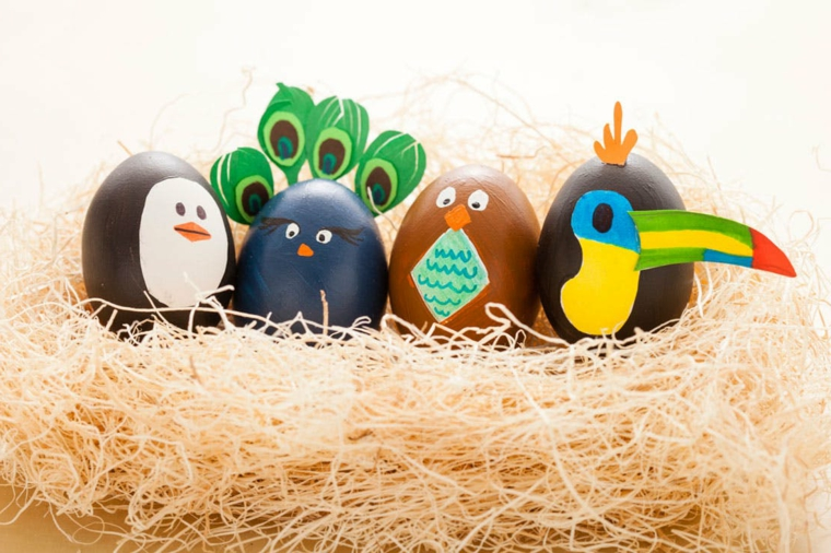 un nido con delle uova pasqua a forma di animati, un pinguino e un pavone, un gufo e un merlo