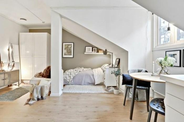 Soggiorno classico in un ambiente open space, mansarda con soffitto in pendenza di colore bianco