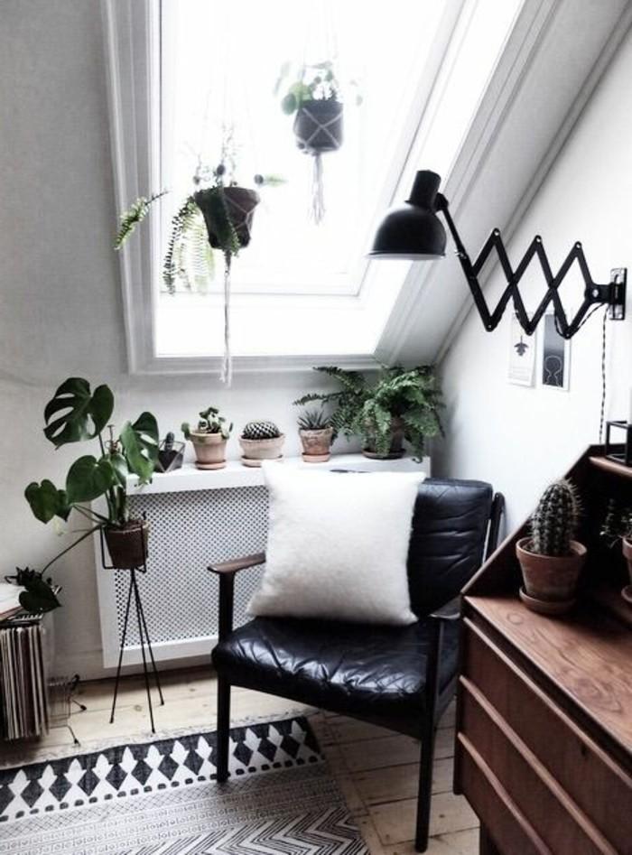 Mansarda con soffitto in pendenza con mobili in legno e poltrona in pelle
