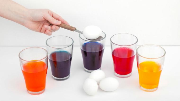 Uova di colore bianco cotte, bicchieri di vetro con una miscela di colorante alimentare e acqua