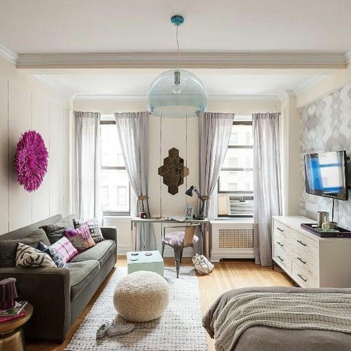 Come arredata il salotto con un divano e letto, mobile tv di colore bianco e tende grigie