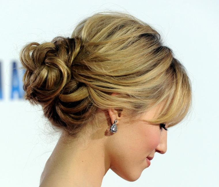una ragazza di profilo con una chignon basso, la frangia morbida e degli orecchini piccoli pendenti