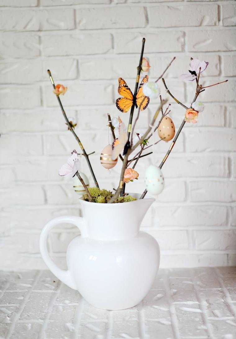 idea per realizzare addobbi pasquali fai da te, una caraffa bianca con dei rami fioriti, fiori, farfalle e uova