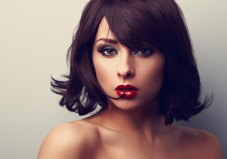 Capelli di colore castano intenso, frangia e mosso sulle punte, donna con rossetto rosso