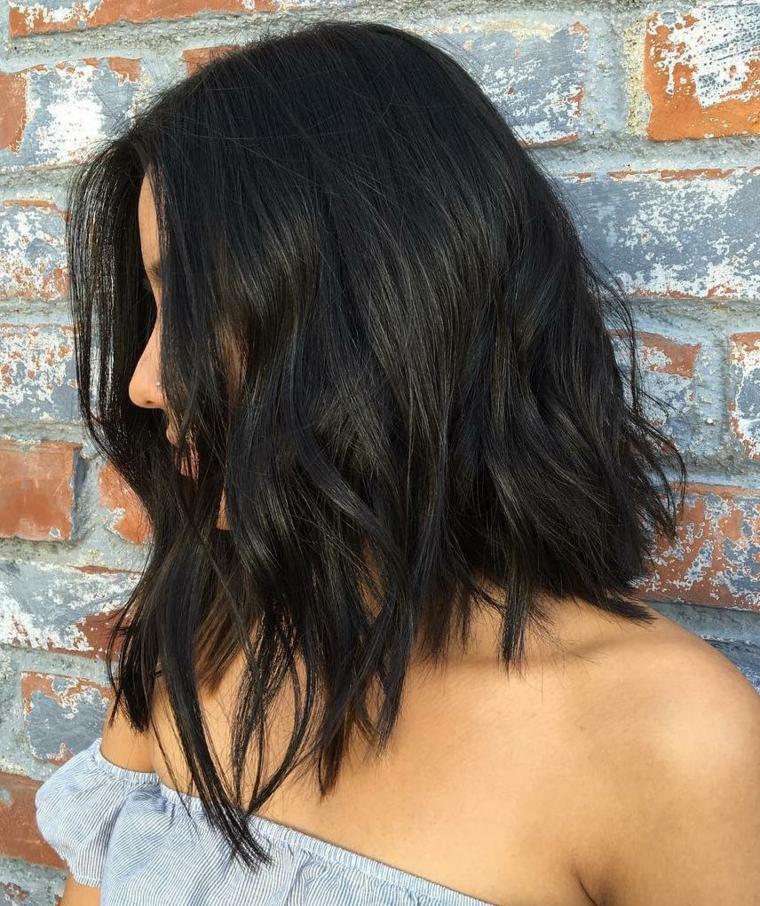 Taglio corto dietro e lungo davanti per dei capelli tinti di colore nero intenso