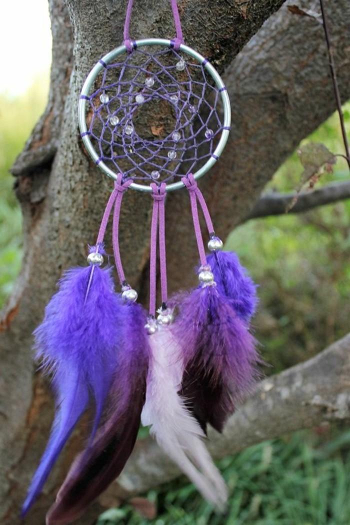 un albero con appeso un originale cattura sogni con piume e perline viola