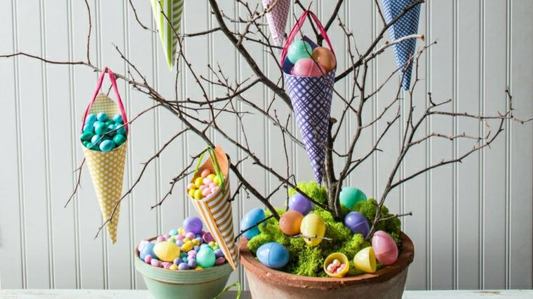 un vaso con delle uova colorate e dei rami con appesi dei coni con ovetti, un'idea per alberi di pasqua originali