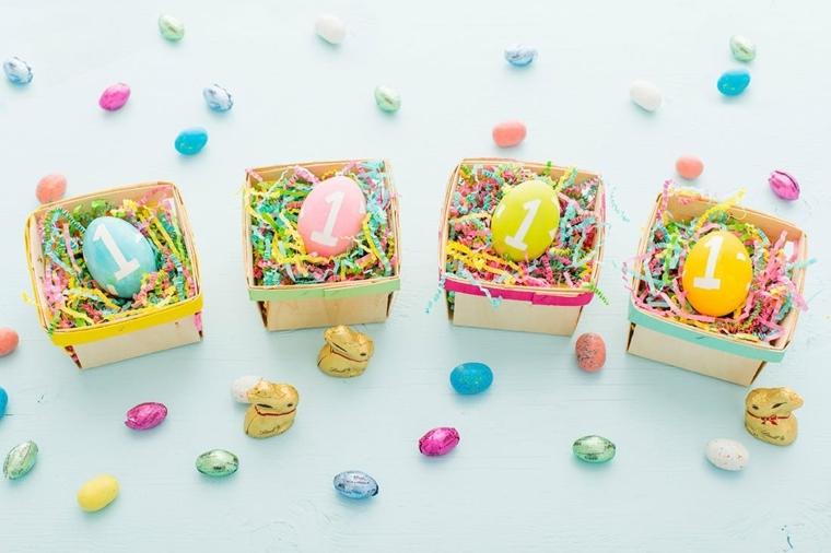 delle scatoline di carta con all'interno delle decorazioni pasquali realizzate con delle uova colorate con il numero uno