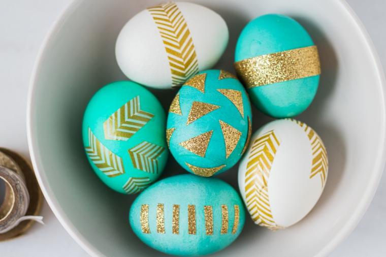 un esempio per uova di pasqua disegno realizzato applicando degli inserti dorati su fondo bianco e azzurro