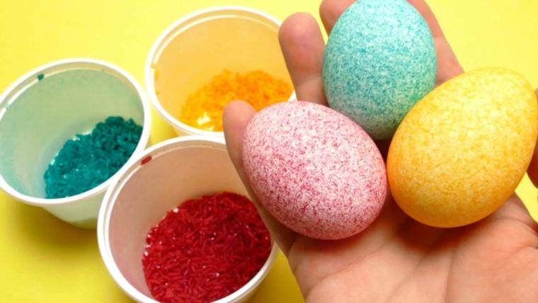 dei contenitori con glitter colorati e delle uova pasqua gialle, rosso e azzurre