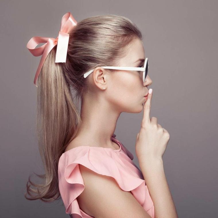 una ragazza di profilo con una coda di cavallo legata con un nastro rosa: idea per delle pettinature capelli facile