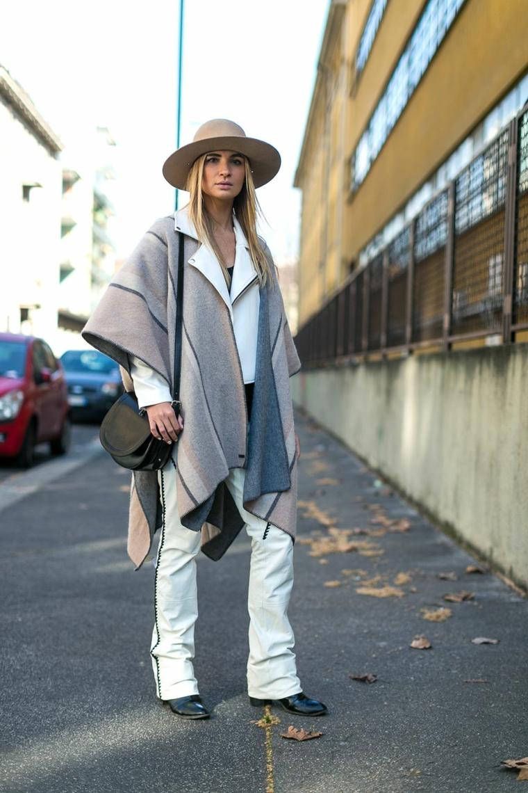 Boho style con poncho e cappello nella stessa tonalità di colore, jeans bianchi a zampa con decorazioni laterali