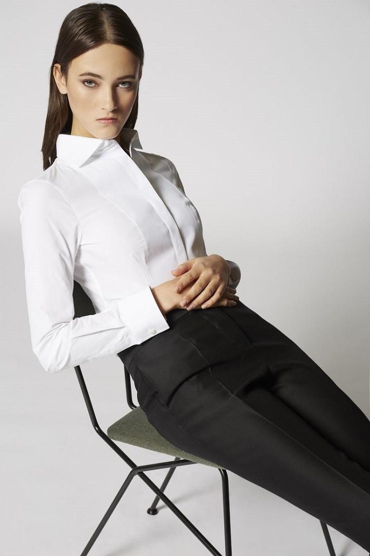 Donna vestita in modo elegante con pantalone nero e camicia bianca