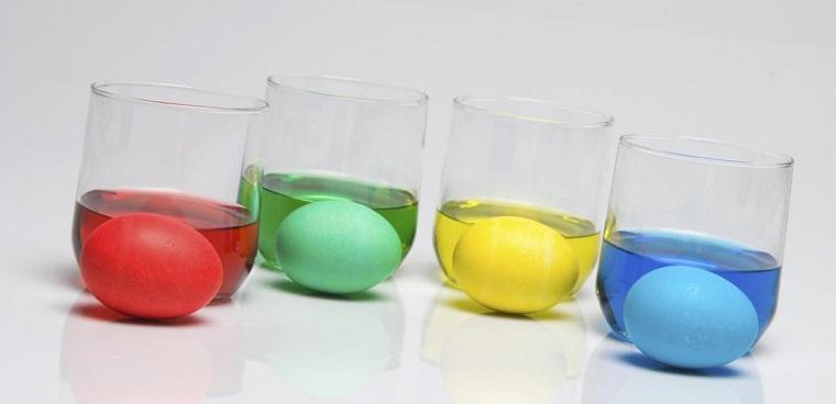 Bicchieri con acqua e colorante alimentare, uova bianche cotte, lavoretti di pasqua
