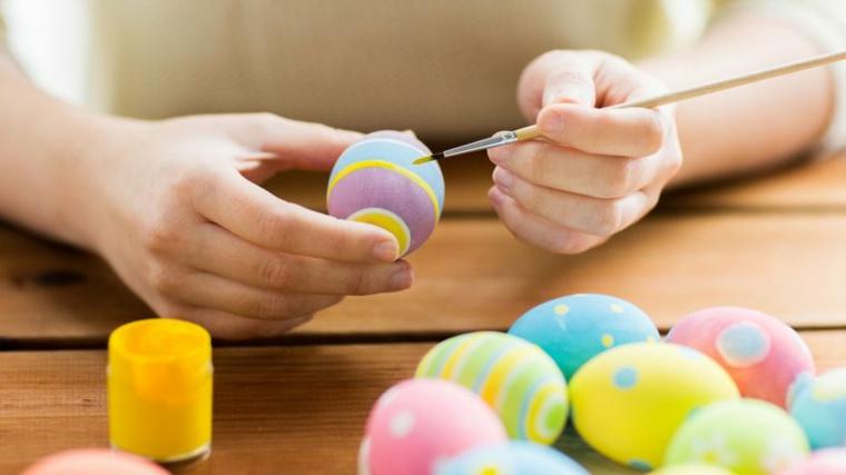 Uova cotte da dipingere con dei colori a tempera, tavolo di legno e donna che dipinge