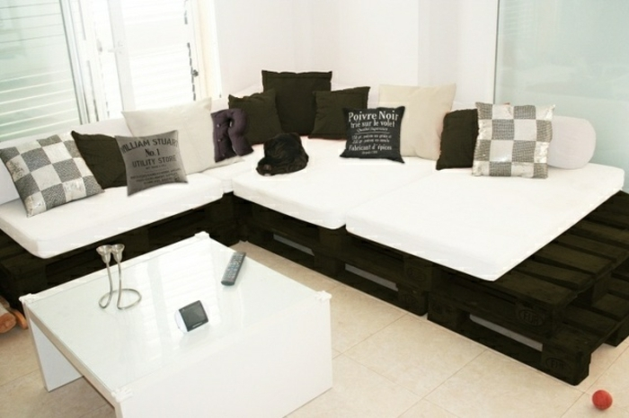 Divano ad angolo in pallet di colore nero, cuscineria bianca e tavolino basso quadrato