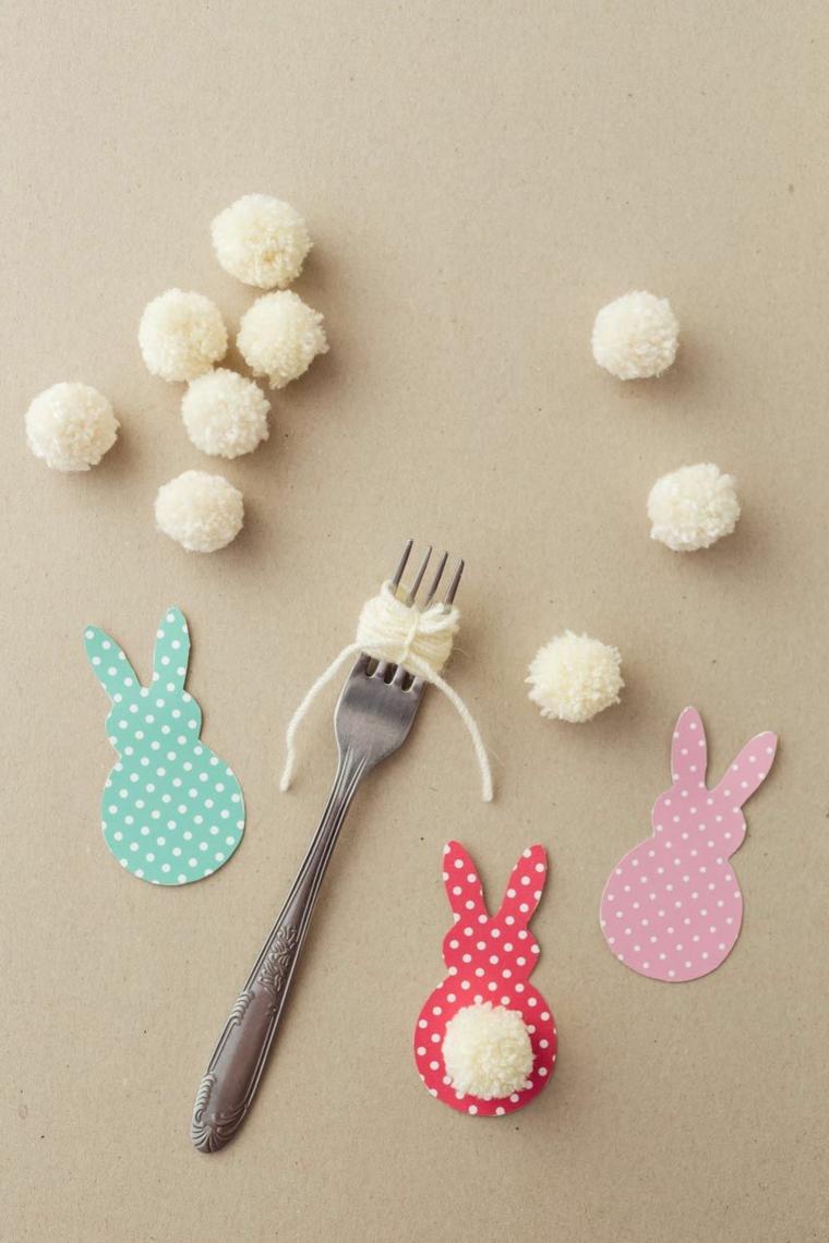 Realizzare pom poms con filo di lana bianco e una forchetta, coniglietti di carta colorata con coda