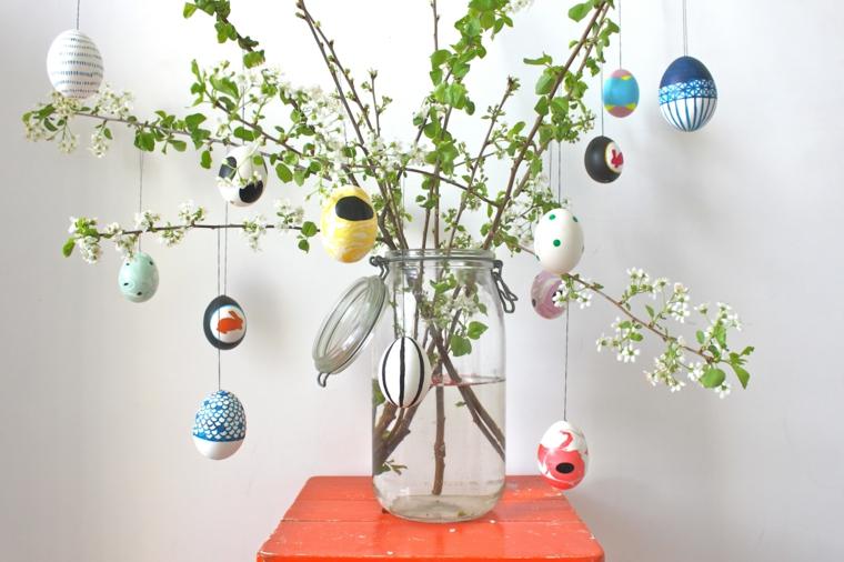 un vaso di vetro per le conserve con all'interno dei rami fiorito addobbati con uova decorate