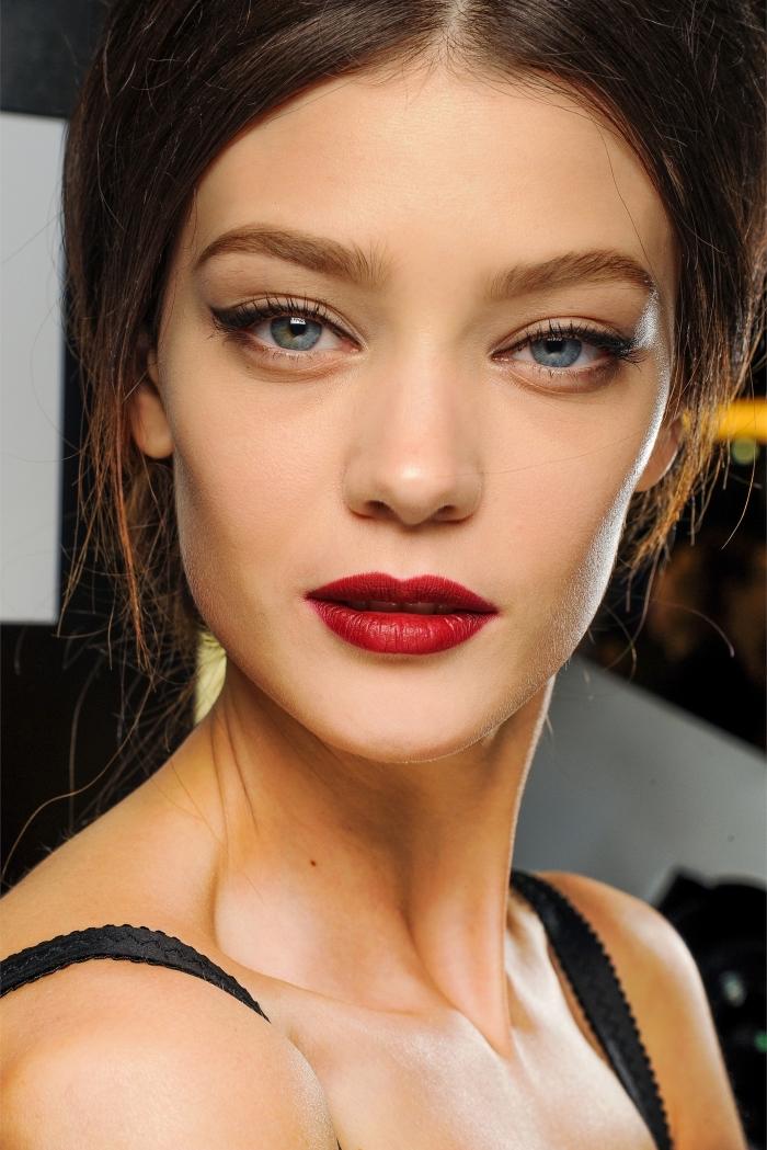 una proposta di makeup rossetto rosso con gli occhi blu truccati con dell'eye liner nero