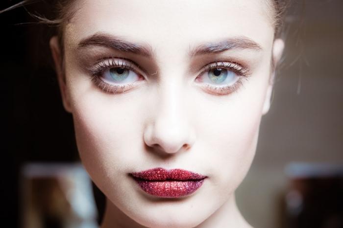 labbra dipinte di rosse con dei glitter, occhi azzurro-verdi truccati con del mascara nero e matita bianca