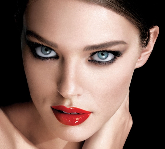 una ragazza dagli occhi blu truccati con della matita nera mentre le labbra sono rosso fuoco