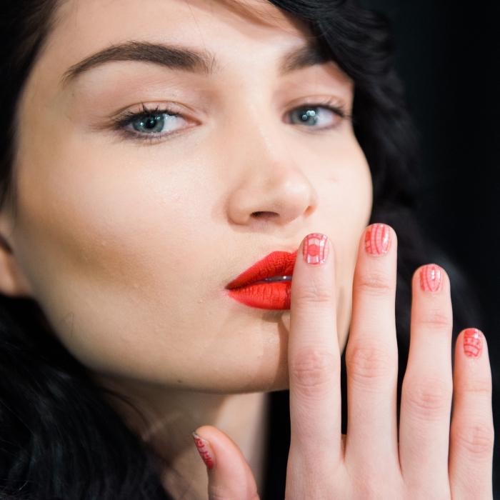 una ragazza con gli occhi blu, una nail art natalizia e il rossetto rosso-arancio