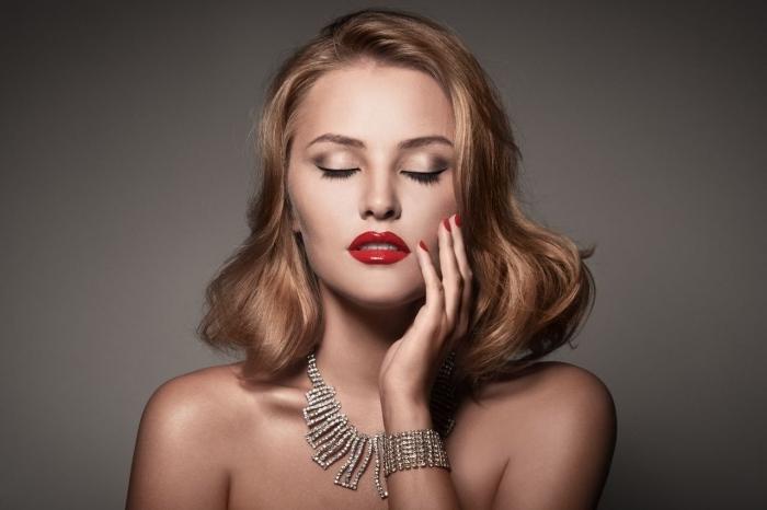 makeup con rossetto lucido rosso, ombretto dorato e rimmel nero, collana e bracciale in brillanti