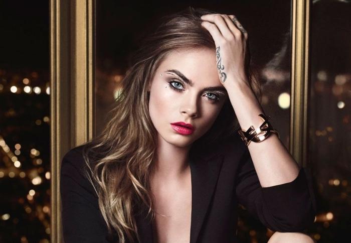 una ragazza con i capelli castano chiari e gli occhi blu, le labbra dipinte di rosso e un tattoo sulla mano