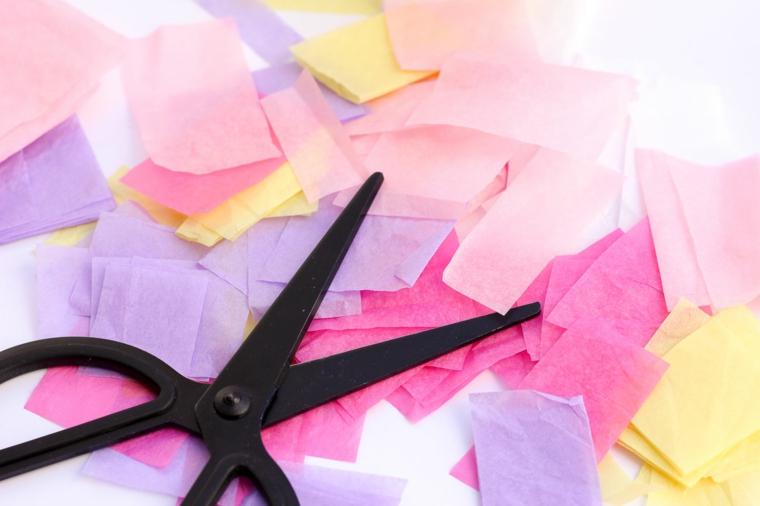 Carta crespa di cario colore ritagliata in piccoli pezzettini, forbice di colore nero