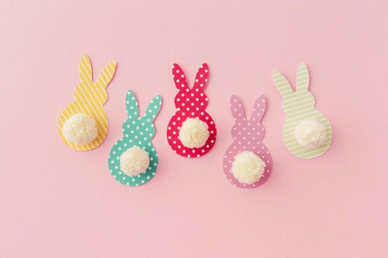 Carta colorata ritagliata a forma di coniglietti, coda di pom poms di colore bianco