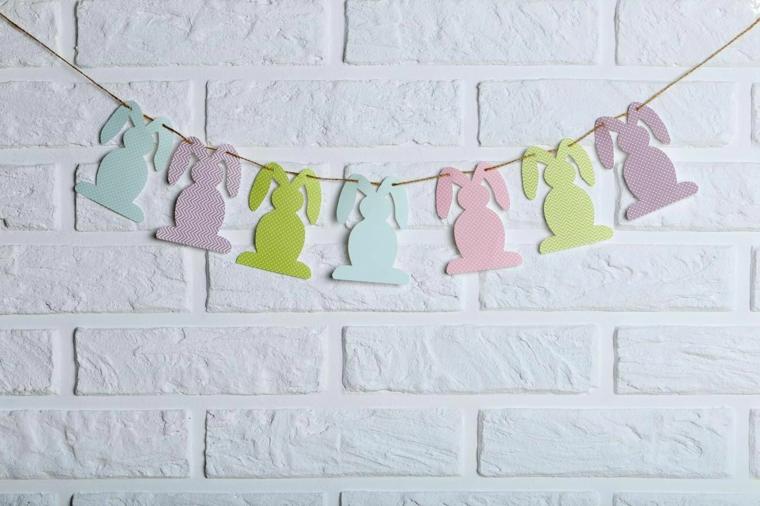 Ghirlanda di coniglietti pasquali, carta colorata e una parete rustica di colore bianco