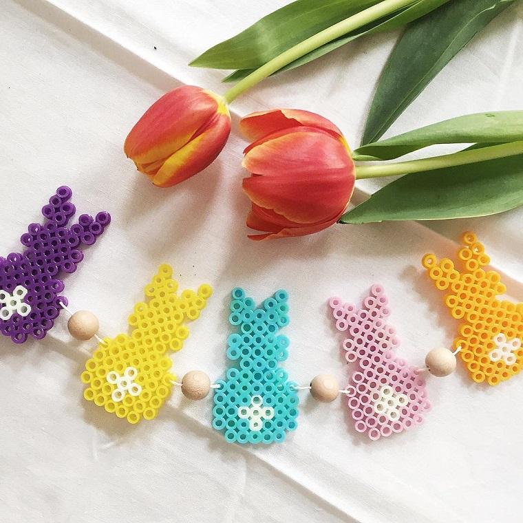 Ghirlanda di coniglietti di vario colore, palline di legno e tulipani con foglie verdi e petali rossi giallo
