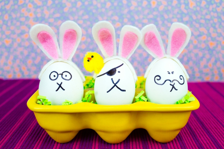 una scatola per le uova gialla con all'interno degli addobbi pasquali realizzati con delle uova con orecchie e muso da coniglio