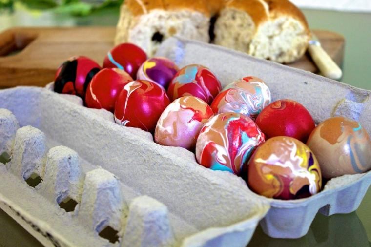 tante uova colorate utilizzando lo smalto per unghie di vari colori, rosso, bianco, oro, viola e nero