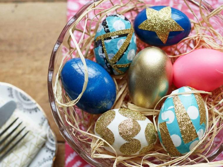 una ciotola di vetro con delle immagini uova di pasqua blu, rosse, bianche, azzurro e oro con delle decorazioni dorate