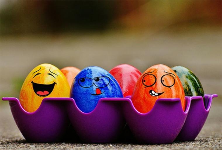 un esempio di immagini uova di pasqua colorate di giallo, blu, verde, rosso e arancio con disegnate delle faccine simpatiche