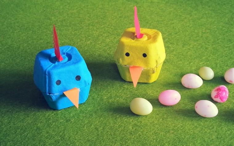 delle scatole per le uova colorate di azzurro e di giallo trasformati in galline con il becco, la cresta e gli occhi neri