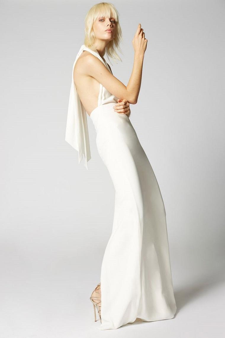 Modella bionda con un vestito di colore bianco, schiena scoperta e tacchi alti