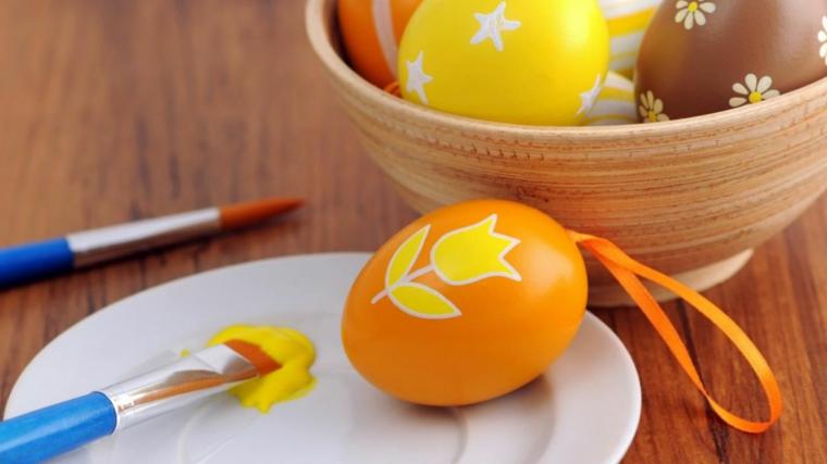 Uovo pasquale dipinto con colori a tempera gialla, fiorellini e stelline come decorazione