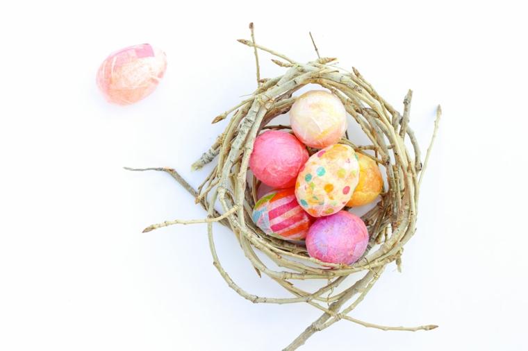 Cesto con delle uova decorate con carta crespa colorata, lavori per pasqua fai da te