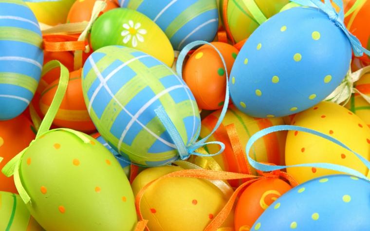 idee fai da te per addobbi pasquali con le uova colorate di giallo, arancione e azzurro e decorate con pois, righe e nastrini