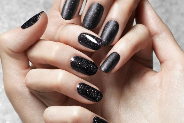 Idea per unghie estive di colore nero, effetto glitter, mani donna con manicure forma a mandorla
