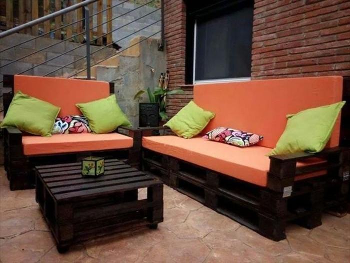 Idea divano bancali di colore scuro, materassi di colore arancione e cuscini verdi