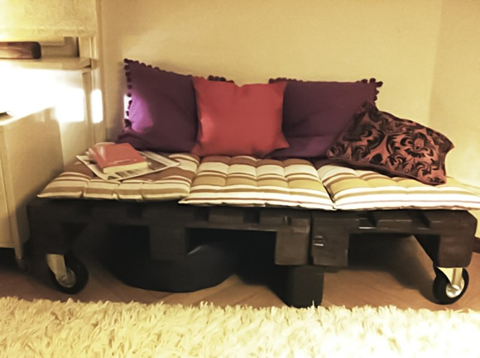 Idea arredamento con un bancale di legno utilizzato come divano, cuscini colorati come schienale