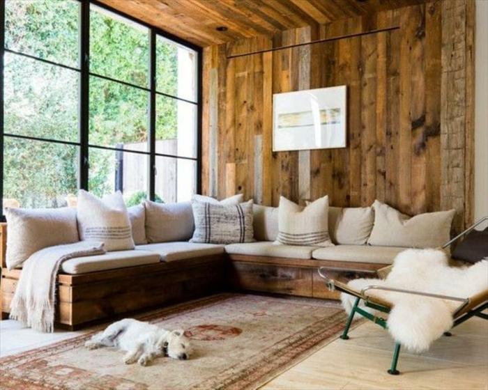 Soggiorno con un divano in pallet e cuscini di colore chiaro, ambiente rustico