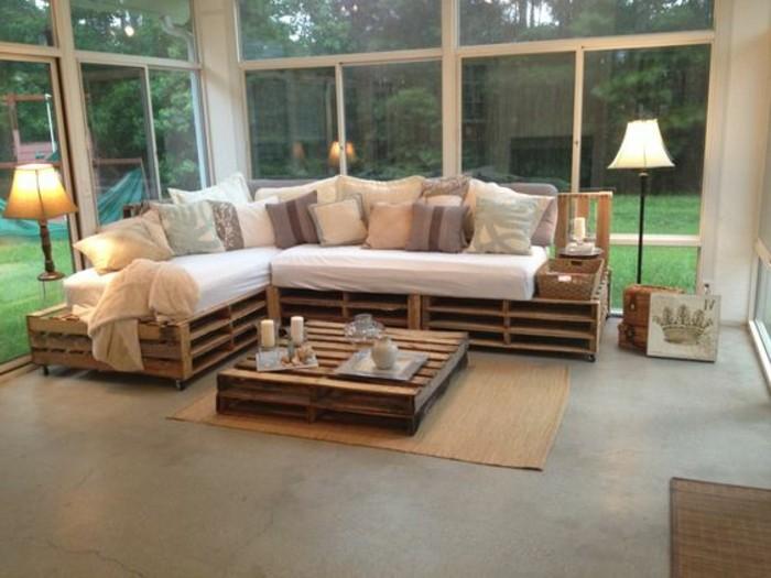 Arredamento con divano pallet fai da te, materassi e tanti cuscini, tavolino basso su tappeto beige