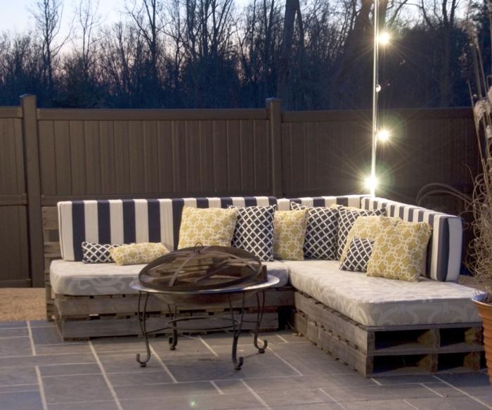 Arredamento esterno con un divano in pallet, cuscineria morbida e colorata