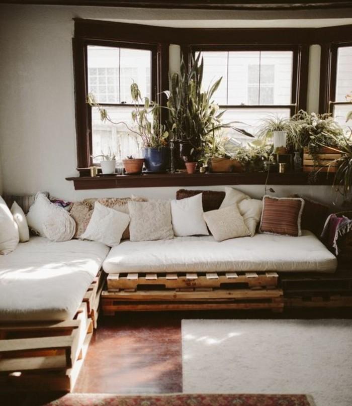 Idea divani in pallet con schienale basso, tanti cuscini di colore chiaro per conferire confort