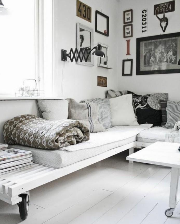 Arredamento soggiorno con un bancale di legno di colore bianco, parete decorata con quadri